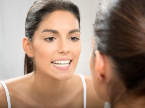Brunette Checking Teeth in Reflection
