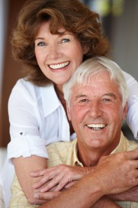 Older Couple Embracing and Smiling At Camera
