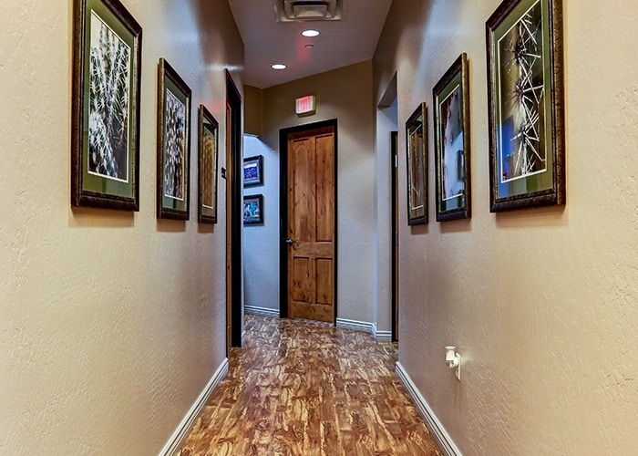view of hallway with photo frames on wall