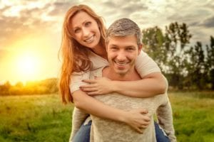 Man Carrying Woman And Both Smiling