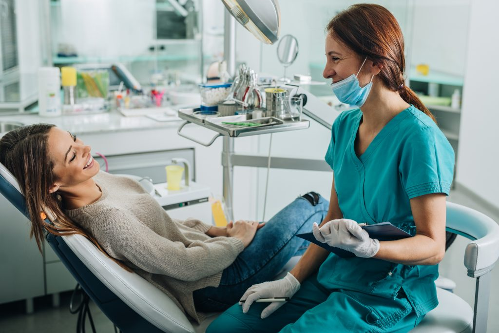 Female-dentist-talking-to-her-patient-at-dentist's-office.