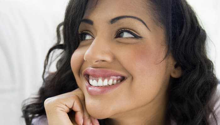 woman smiling widely and looking away from camera
