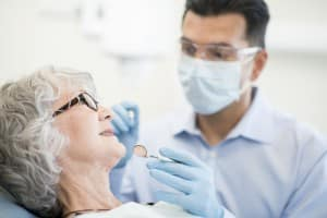 Dentist Preparing Examination of Mature Female